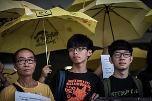Student protesters Joshua Wong (Centre) and Nathan Law (Right) stand outside the court of justice in Hong Kong. Wong appeared in court on August 28 over an anti-China protest in June 2014, a day after he faced fresh charges over his participation in