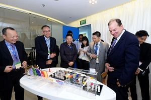 Looking at some items reproduced by 3D printers are EDB executive director of precision engineering Chang Chin Nam (far left); EDB assistant managing director Lim Kok Kiang (second from left); EDB head of precision engineering Kelvin Zin (third from