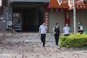 Police investigators inspect the area around a damaged building the day after a series of blasts in Liucheng county in Liuzhou, Guangxi province, on Oct 1, 2015.