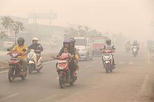 Motorcyclists riding without masks at around noon yesterday in Palangkaraya, Central Kalimantan, where the PSI reached 1,801 in the afternoon and visibility was down to about 100m.