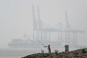 A Malaysian man fishing in the backdrop of gantry cranes shrouded with haze in Port Klang on Oct 1, 2015.