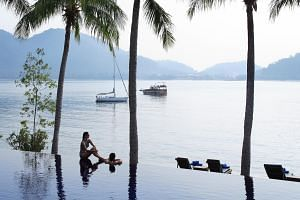 Lounge on a beachchair by the sea (left) or enjoy the sea breeze from the villa (above). Pangkor Laut Resort is set on a private island filled with lush rainforests.