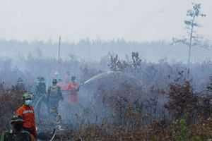 Indonesian firefighters backed by soldiers extinguish a fire over burning peat land in the district of Banjar in Southern Kalimantan province on Borneo island in this photograph taken on Sept 23, 2015.