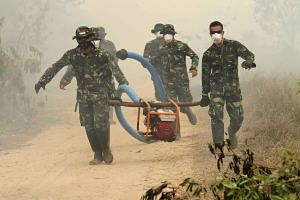 Indonesian soldiers carrying a gas powered water pump used to help extinguish a peatland fire in Ogan Ilir, South Sumatra province on the island of Sumatra, on Sept 30, 2015.