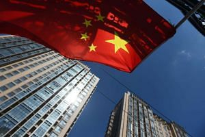 A Chinese flag flies near apartment buildings in Beijing on Sept 11, 2015.