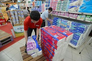 Staff removing APP-related products from shelves at FairPrice's outlet at Nex mall in Serangoon yesterday. Late last month, the National Environment Agency began legal action against APP and four Indonesian firms it believes to be behind the haze-cau
