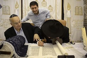 Mr Harry Elias (left) symbolically finishing the writing of a new set of Torah by holding on to the hand of Rabbi Mendy Goldshmid (right) as Mr Daniel Harel, who donated the set, watches. Rabbi Goldshmid, who is based in Koh Samui, flew here for the