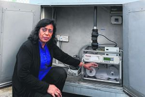 Mrs Indrani Rajaram with a machine used by NEA to help measure the concentration of PM2.5 in the air. Converting raw pollutant concentration data into one-hour PSI readings is not supported by health studies, she said.