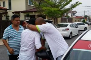 Family members of the kidnapped boy hugging the taxi driver (right).