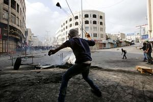 A Palestinian protester throws stones during clashes with members of the Israeli armed forces in the West Bank city of Hebron, Oct 9, 2015.