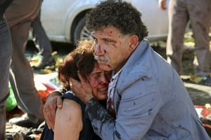 An injured man hugs an injured woman after an explosion during a peace march in Ankara, Turkey on Oct 10.