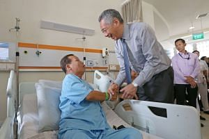 PM Lee Hsien Loong visits patients including (left) Chionh Koek, 62, after the official opening of the Ng Teng Fong General Hospital and Jurong Community Hospital.