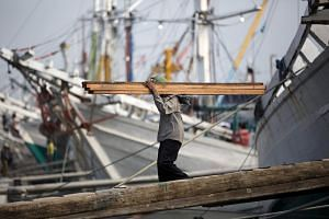 A labourer unloads timber from Kalimantan province from a phinisi, a traditional Indonesian ship, at Sunda Kelapa port in Jakarta in this Sep 8, 2014, file photo