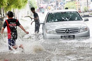 Children play in floodwaters near a stranded a car in Tanjung Duren, West Jakarta, on Jan 31, 2015.