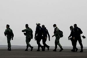Singapore military and civil defence personnel walking towards a Republic of Singapore Air Force Chinook helicopter at a haze-shrouded airbase in Palembang on Sumatra island yesterday. They were headed for their first aerial water-bombing mission ove