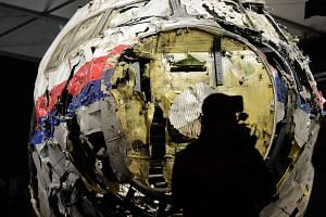 Members of the media take a look inside the reconstructed cockpit of Malaysian Airlines flight MH17 during a presentation of investigation results at Gilze Rijen airbase on Oct 13, 2015.