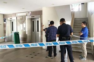 Policemen inspecting the site where an elderly woman's hand was severed by a lift, in Jurong, on Oct 9, 2015.