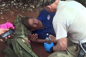 A handout photo taken and released by the Western Australia Police on Oct 13, 2015, shows Reg Foggerdy being comforted by police trackers after he was found.Foggerdy was missing for six days in a remote Australian desert. He survived by eating black