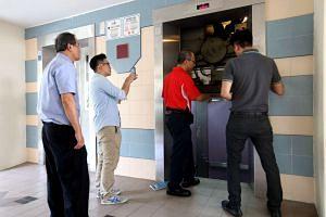 Lift service repairmen inspecting the lift B at block 322 Tah Ching Road.