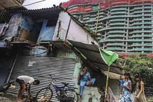 A slum next to a luxury tower construction site in the Parel area of Mumbai on Aug 8, 2014.