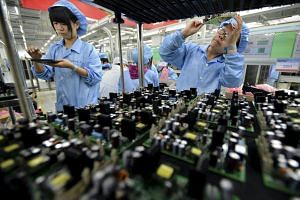 Employees work at a production line of electronic panels at a factory of FiberHome Technologies Group, in Wuhan, China.