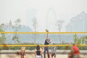 People playing volleyball at 4pm yesterday at the Singapore Sports Hub. The 24-hour PSI entered the unhealthy range in the afternoon.