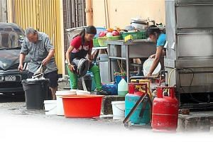 Restaurant workers washing plates and utensils in the back lane.