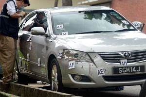 An investigation officer looking into a silver Toyota Camry which was found abandoned at Eunos Avenue 7 on July 11, 2013.