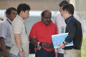 Govindasamy Nallaiah (centre), who stands accused for the murder of Madam Low Foong Meng, being taken back to the scene in 2011.