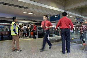 SMRT staff ushering commuters at Ang Mo Kio MRT on Jan 20, 2014.
