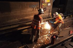 An MTR maintenance crew working to replace a section of rail at Diamond Hill station in the early hours of a Saturday morning. ST PHOTO: LI XUEYING