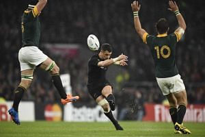 New Zealand's fly half Dan Carter kicks and scores a drop goal.