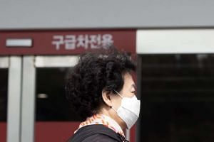 A Korean woman wearing a face mask walks past an emergency room at Seoul National University Hospital, South Korea, on Oct 13, 2015.