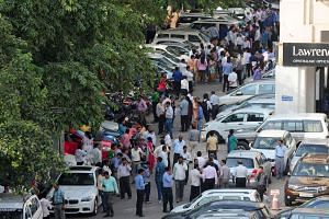 Indian office workers stand in an open area in a car park following an earthquake, in New Delhi on Oct 26, 2015