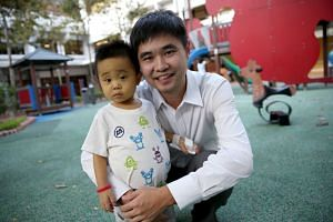 In this July 30, 2015, photo, 22-month-old Jeremy is held in his father's arms two days before the liver transplant at NUH. His father, Guo Yang, is donating part of his liver to save his son's life. Jeremy, his stomach bloated and skin jaundiced