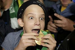 A boy displays the winners' medal given to him by Sonny Bill Williams of New Zealand after the Rugby World Cup Final.