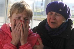 Relatives react at Pulkovo international airport outside Saint Petersburg, Russia.