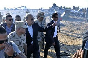 Egyptian Prime Minister Sherif Ismail (third left) examines the wreckage at the site of the Russian plane crash.