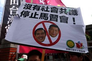 A Taiwanese protester displays a banner against Taiwanese President Ma Ying-jeou (left) and Chinese President Xi Jinping (right).