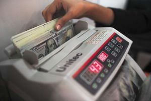 A currency exchange clerk counts US dollar notes.