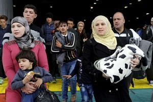 Refugees and migrants disembark a passenger ship in Greece on Nov 1 2015.