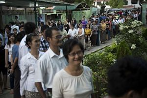 People queue to cast their vote at a polling station in Yangon on Nov 8, 2015.