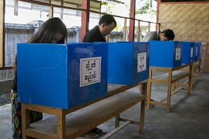 People prepare to cast their ballots during advanced voting at a polling station of Myit Kyi Na township in Kachin State, northern Myanmar, Nov 7, 2015.