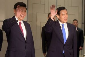 Chinese President Xi Jinping (left) and Taiwanese President Ma Ying-jeou wave to photographers as they enter the room at the Shangri-la Hotel in Singapore on Nov 7, 2015.