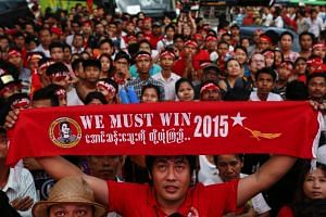 Supporters of National League for Democracy (NLD) party celebrate in front of the NLD headquarters a day after general elections in Yangon.