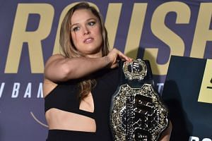 Ronda Rousey picks up her championship belt before a face-off for the UFC fight in Melbourne on Nov 13, 2015.