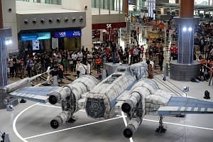 Star Wars fans having a field day at Changi Airport where they came face to face with Stormtroopers (above) and a scale model of the TIE Fighter (top). Singapore is the first Asian stop outside of Japan for the Star Wars-themed All Nippon Airways pla