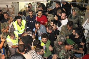 Emergency personnel remove a body from the site of the twin suicide bombing.