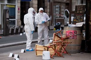Police forensic experts work at the scene of one the shootings, at the Cafe Comptoir Voltaire in Paris, on Nov 14, 2015.