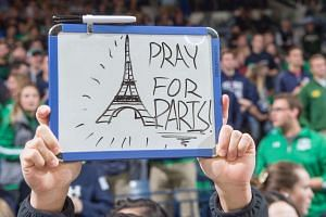 "A student holding up a ""Pray for Paris"" sign before a university football game in the US."